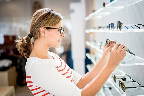 Casual young woman shopping for glasses at the optics and looking very happy